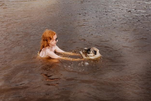 Rudowłosa dziewczyna uczy mopsa pływać w rzece.