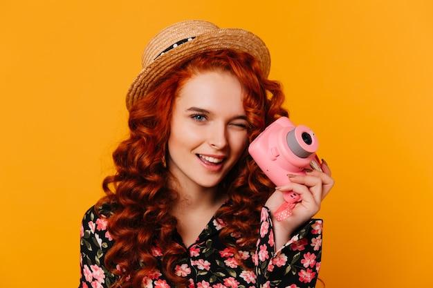 Rudowłosa dziewczyna w bluzce i bluzce w kwiatowy wzór mruga i trzyma różowy aparat na pomarańczowej przestrzeni.