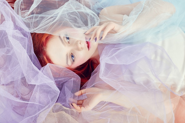 Rudowłosa dziewczyna w jasnej sukience w kolorze powietrza leży na podłodze, portret z bliska
