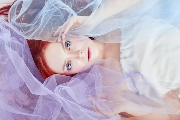 Rudowłosa dziewczyna w jasnej sukience w kolorze powietrza leży na podłodze