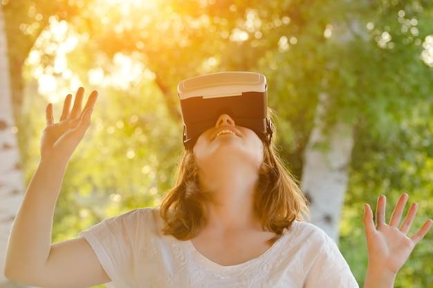 Rudowłosa dziewczyna w kasku wirtualnej rzeczywistości patrząc w górę