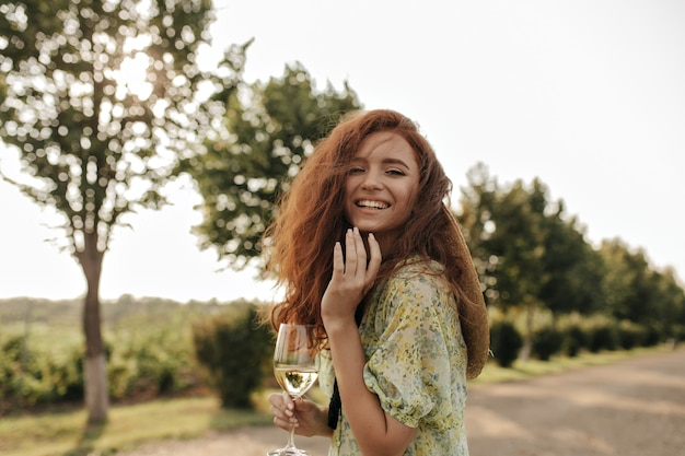 Rudowłosa dziewczyna w letnich żółtych i zielonych nowoczesnych ubraniach, patrząca z przodu, śmiejąca się i trzymająca kieliszek z winem na świeżym powietrzu