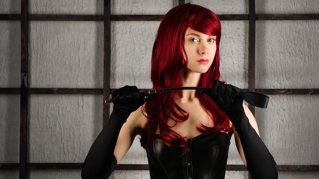 Rudowłosa dziewczyna w skórzanym gorsecie trzyma klapsa. strój bdsm