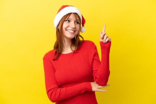 Rudowłosa dziewczyna w świątecznym kapeluszu na żółtym tle wskazująca świetny pomysł