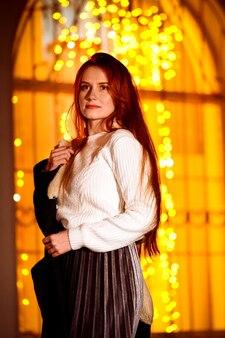 Rudowłosa dziewczyna w zimowy wieczór na ulicy