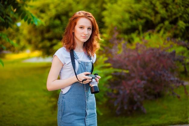 Rudowłosa dziewczyna z aparatem fotograficznym w parku
