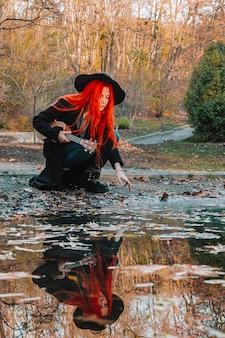 Rudowłosa dziewczyna z długimi włosami gra na ukulele w parku. szkoła, koncepcja edukacji muzycznej, uczeń uczy się grać na instrumencie smyczkowym.