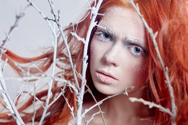 Rudowłosa dziewczyna z długimi włosami, twarzą pokrytą śniegiem z szronem