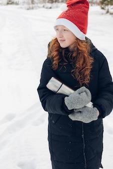 Rudowłosa dziewczyna z termosem pije herbatę na zimowy spacer.