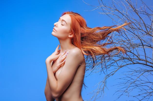 Rudowłosa dziewczyna z włosami w suchych gałązkach. koncepcja pielęgnacji włosów.