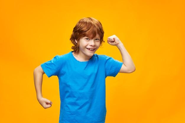 Rudowłosa dziewczynka gestykuluje rękami dla zabawy