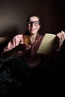 Rudowłosa dziewczynka imbir, czytanie książki, leżąc na kanapie i śmiejąc się