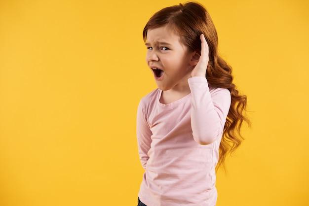 Rudowłosa dziewczynka kładzie dłoń na uchu.
