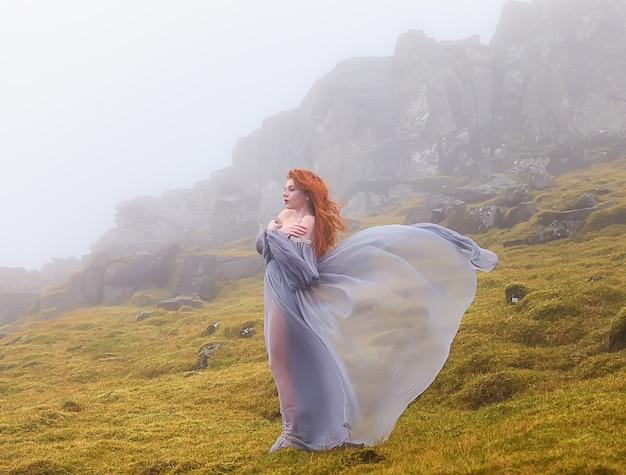 Rudowłosa elfka w fantazyjnych ubraniach pozostaje w pobliżu skały w mglisty dzień wyspy owcze w danii
