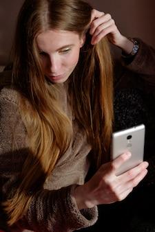 Rudowłosa imbirowa dziewczyna w bluzie robi selfie na smartphone, siedzi na kanapie i uśmiecha się
