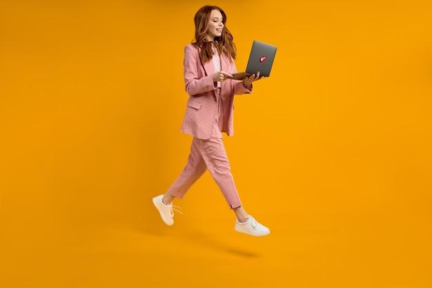 Rudowłosa kobieta biegać, skakać, pisząc na laptopie, ubrana w elegancki różowy garnitur na żółtym tle w s...