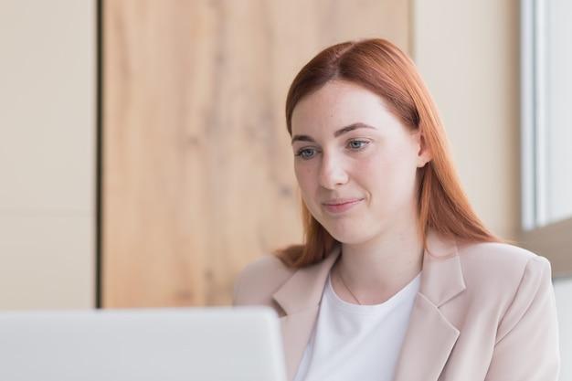 Rudowłosa kobieta biznesu uśmiechnięta siedząc przy komputerze uzyskała zadowalający wynik