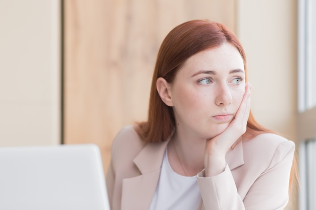 Rudowłosa kobieta biznesu z silnym bólem zęba i bólem głowy przy przepracowaniu komputera
