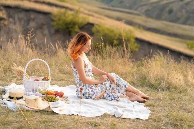 Rudowłosa kobieta cieszy się zachodem słońca na łonie natury. piknik w terenie.