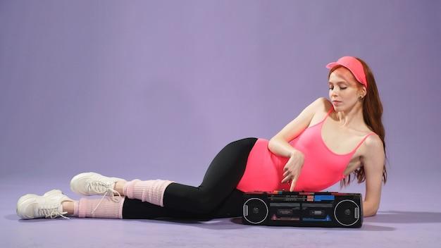 Rudowłosa kobieta fitness z piegami słucha muzyki na podłodze na przenośnym odtwarzaczu audio