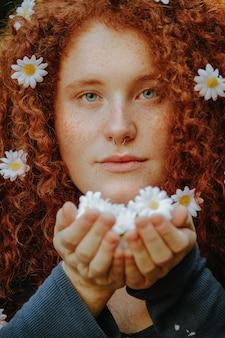 Rudowłosa kobieta gospodarstwa stokrotki kwiaty