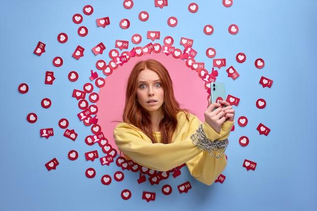 Rudowłosa kobieta ma obsesję na punkcie internetu. kobiece ręce związane łańcuchem, które nie interesują się niczym innym jak smartfonem