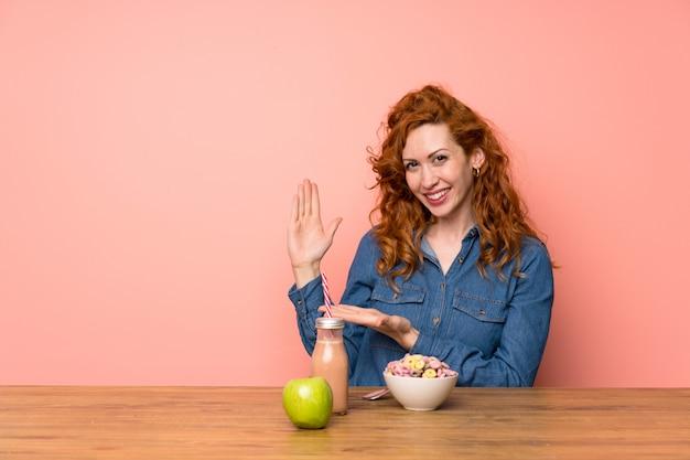 Rudowłosa kobieta mająca płatki śniadaniowe i owoce wyciągające ręce na bok, aby zaprosić do siebie