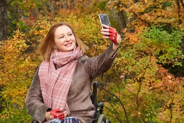 Rudowłosa kobieta na wózku inwalidzkim robi selfie na telefon