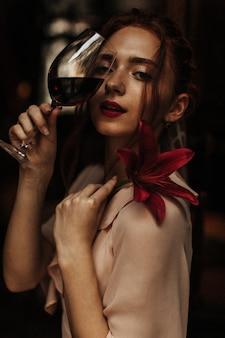 Rudowłosa kobieta pozuje z kwiatem i kieliszkiem wina