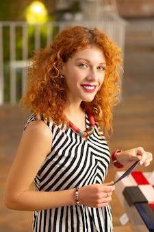 Rudowłosa kobieta. rudowłosa atrakcyjna uśmiechnięta bizneswoman nosząca naszyjnik stojący w swoim sklepie