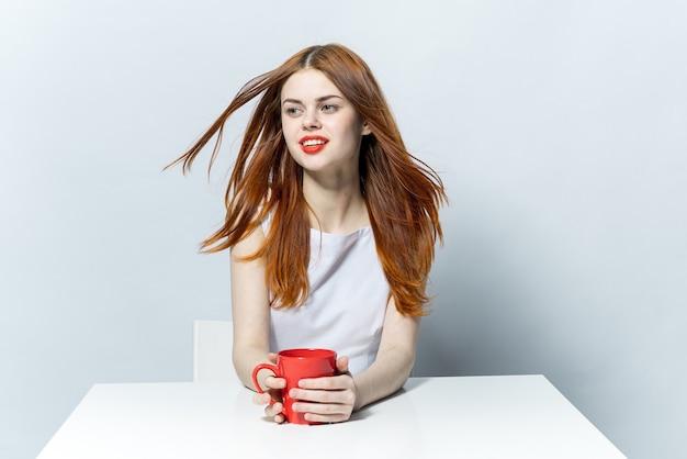 Rudowłosa kobieta siedzi przy stole przy filiżance drinka relaksacyjnego
