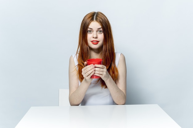 Rudowłosa kobieta siedzi przy stole przy filiżance napoju relaksacyjnych emocji