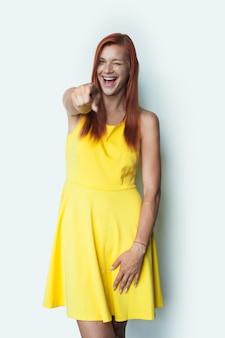 Rudowłosa kobieta uśmiecha się do kamery, mrugając i wskazując na sobie sukienkę na białej ścianie studia