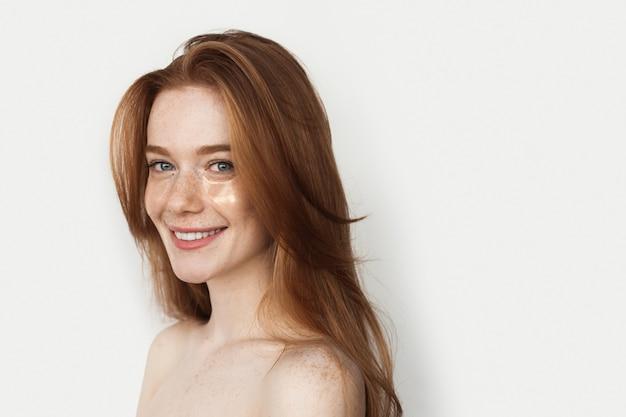 Rudowłosa kobieta uśmiecha się nosząc hydrożelowe opaski na oczy na białej ścianie