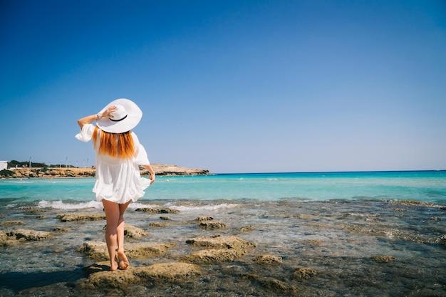 Rudowłosa kobieta w białej sukni stoi nad brzegiem morza śródziemnego