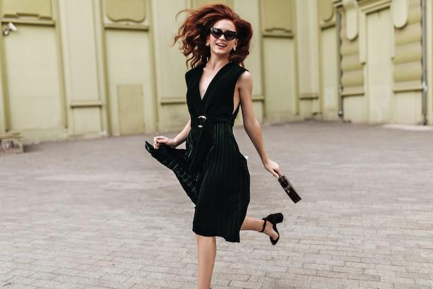 Rudowłosa kobieta w ciemnozielonej sukience na zewnątrz