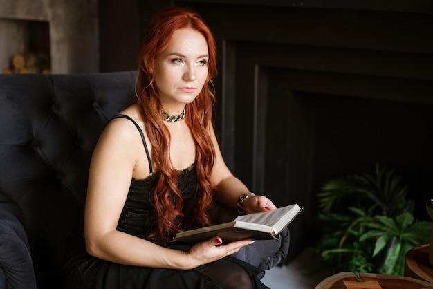 Rudowłosa kobieta w czarnej sukience na krześle czytająca książkę