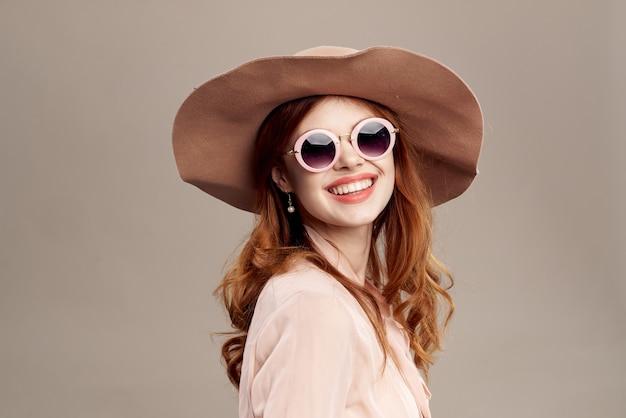Rudowłosa kobieta w kapeluszu i koszuli na beżowym makijażu uśmiech urok moda młodzieżowa.