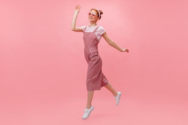 Rudowłosa kobieta w kombinezonie i okularach radośnie porusza się na różowym tle.