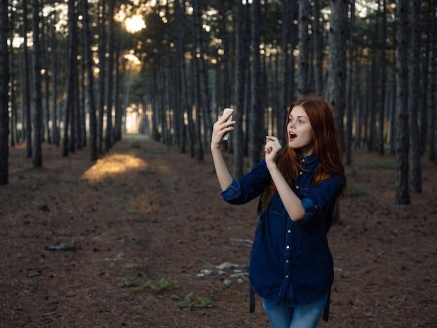 Rudowłosa kobieta w lesie natura podróż spacer wolności. zdjęcie wysokiej jakości
