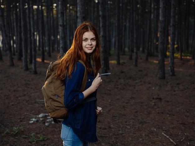 Rudowłosa kobieta w niebieskiej koszuli w sosnowym lesie z plecakiem na plecach.