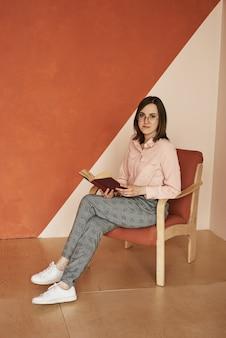Rudowłosa kobieta w okularach i różowej koszuli siedzi na fotelu i prowadzi książkę pomarańczową żółtą ścianą