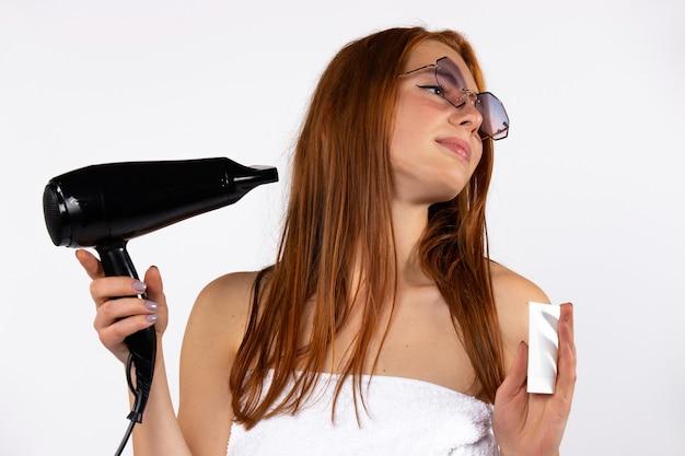 Rudowłosa kobieta w okularach z suszarką do włosów i kremem przeciwsłonecznym, pozowanie na białej ścianie
