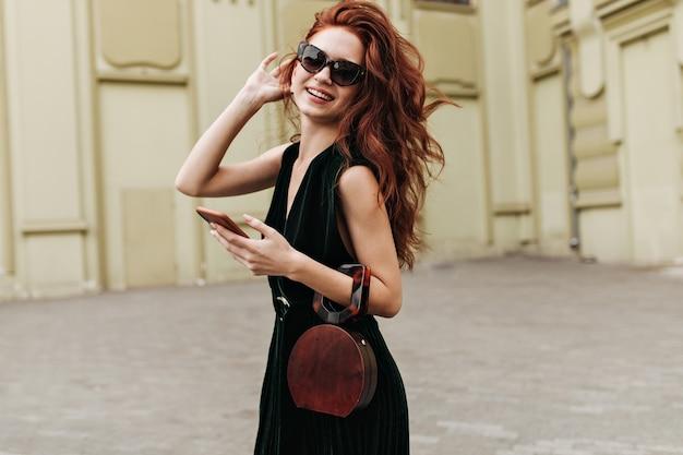 Rudowłosa kobieta w okularach z uśmiechem, trzymając telefon