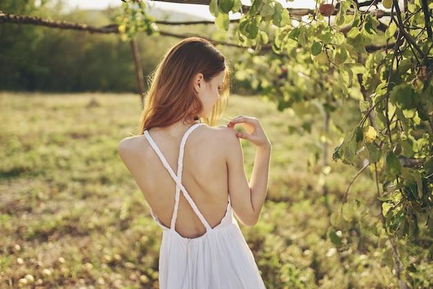 Rudowłosa kobieta w przyrodzie na polu w pobliżu jabłoni