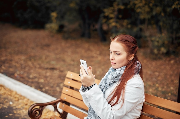 Rudowłosa kobieta w średnim wieku ze smartfonem w dłoni siedzi na ławce w parku i komunikuje się na portalach społecznościowych.