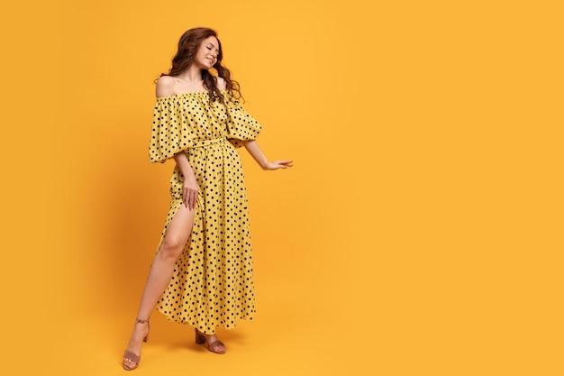 Rudowłosa kobieta w żółtej sukience pozowanie na żółto. letni nastrój