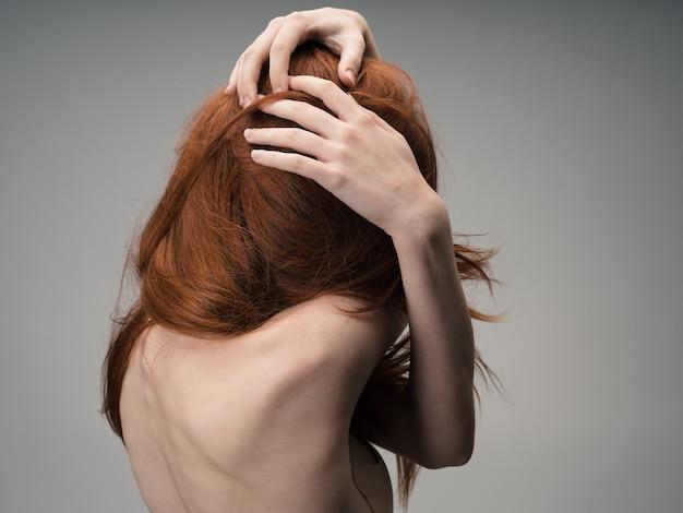 Rudowłosa kobieta z odkrytymi ramionami dotyka jej głowy.