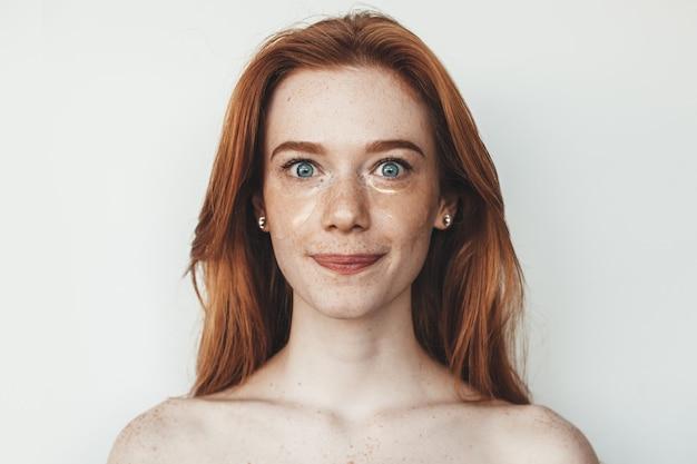 Rudowłosa kobieta z piegami i nagimi ramionami pozująca z hydrożelowymi plamami na oczach na białej ścianie
