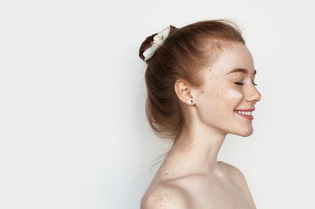 Rudowłosa kobieta z piegami uśmiecha się mając krem przeciw starzeniu się na policzkach pozowanie